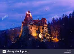 dracula castle with lights at night in romania stock photo