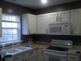 dark gray kitchen walls with white cabinets during white
