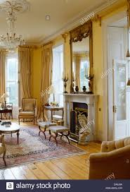 Cream Silk Drapes Marble Bust Beside Fireplace Below Large Antique Mirror In Grand