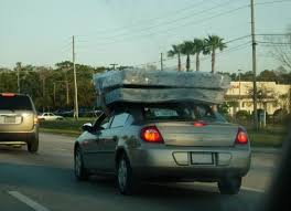 idiot holding mattress on top of car with his hand goes for drive