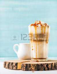 latte macchiato with whipped cream in tall glass with two straws