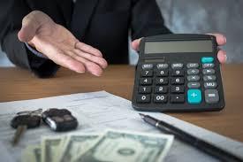 au bureau prix un vendeur de voiture tenant une clé et calculant un prix au