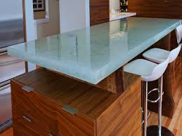 wooden kitchen island with storage and glass countertop along with