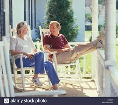 Rocking Chairs On Porch Mature Couple Relaxing On Rocking Chairs On Large Porch Stock