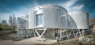 futuristic home made of massive steel cylinders hides two houses