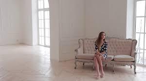fashion model in dress posing siting on elegant sofa in photo