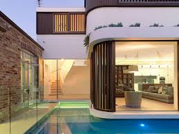 the organic two storey pool house addition at the back of a single
