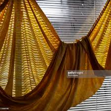 gold colored cloth hanging in front of window blinds stock photo