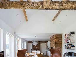 beige sofa gray ottomans floor lamp framed art white side tables
