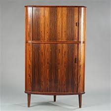 a brazilian rosewood corner cabinet with two sliding doors in
