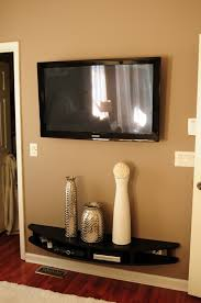 curved black wall mounted media console shelf under flat screen tv