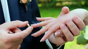 Does The Wedding Band Go Before The Engagement Ring by Closeup Of Bride And Groom Exchanging Wedding Rings Over Green