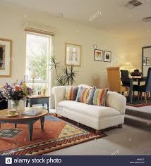 colourful striped cushions on white sofa and patterned rug in