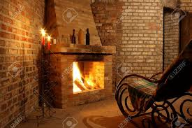 rocking chair by the fireplace in brick room and candles stock