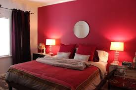 contemporary bedroom with red wall paint circle mirror above bed