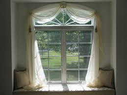 sheer swag treatment over arched window embellished with and