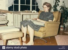 1960s woman fashion sitting in chair in living room stock photo