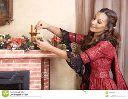 young woman decorates fireplace for christmas eve retro style
