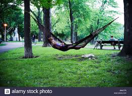 young woman sleeping hammock in lafontaine park montréal stock