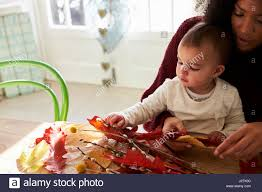 mother and daughter making autumn decoration at home stock photo