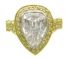 yellow gold pear shape and round diamond engagement ring bezel set