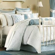 grey bedding sets with carved white iron bed on blue rug added by