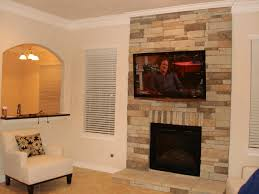 stone fireplaces with tv tv above a stone mantle and shelving on