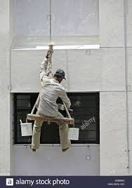 A Painter Is Seating On A Cradle For Building S Exterior Painting
