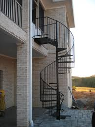 black metal spiral staircase for outdoor in rustic brick stone