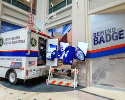 postal vehicles about the exhibit behind the badge
