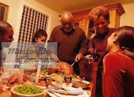 grandfather carving turkey at thanksgiving dinner table stock