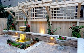 ornate wood trellis brick seat wall paver patio and fountain in