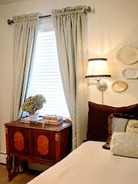 bedroom with swing arm sconce and window curtains choosing the