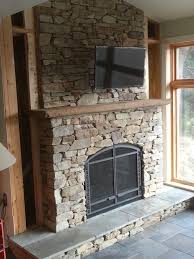 gas fireplace with stacked stone pieced hearth corbels board