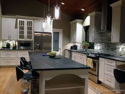 a gorgeous large white kitchen with black marble countertops and a