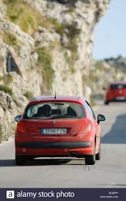 peugeot red rear view of a red peugeot 207 car driving along a road in spain