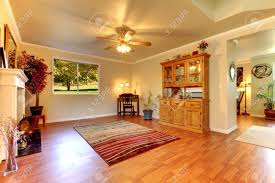 large living room with hardwood floor red rug and beige walls