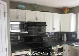 black subway backsplashes tile above l shaped white cabinetry with