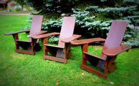 furniture three brown wooden adirondack chairs lake in backyard