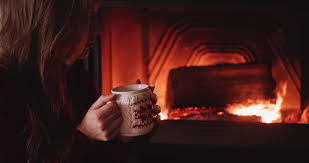 woman drinks coffee or tea from a cup against cozy fireplace in