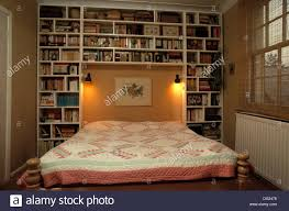 fitted bookshelves beside and above bed with patchwork quilt in
