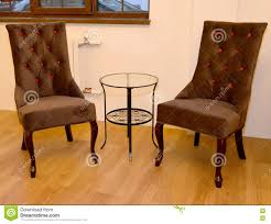 two soft chairs and coffee table stand at a wall in a drawing room