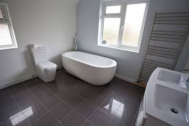 fab oval tub over grey ceramic floor tiled and double windows
