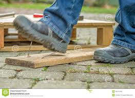 a worker with safety boots steps on a rusty nail royalty free