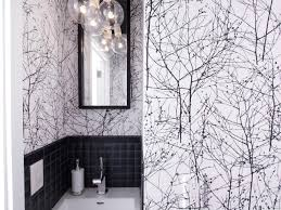 black and white powder room with bold wallpaper tree patterned