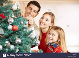 At Home Christmas Trees by Happy Family Decorating Christmas Tree Together At Home Stock