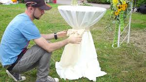 florist man at work tying a bow on white wedding table making a