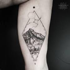 cross tattoos on bicep landscape tattoo on the left inner arm tattoo artist okan uçkun