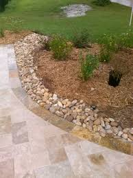using river rock as a driveway landscape border to stop rainwater