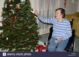 what to get an elderly woman for christmas elderly woman in wheelchair decorating a christmas tree stock